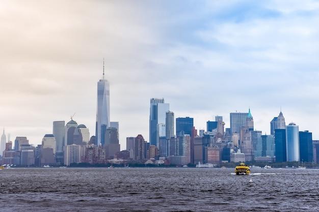 Городской пейзаж финансового района манхэттена с острова свободы, в туманный день.