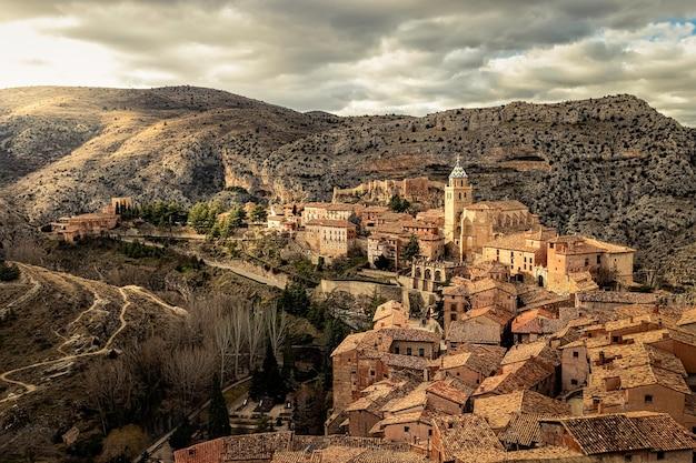Городской пейзаж средневекового города альбарракон с его старыми каменными домами, церквями и атмосферой древнего городка между горами. теруэль, арагон, испания. европа.