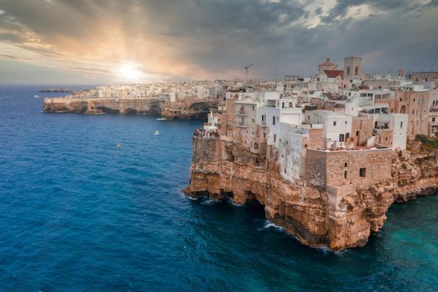 Paesaggio urbano di polignano a mare circondato dal mare sotto la luce del sole e un cielo nuvoloso in italia