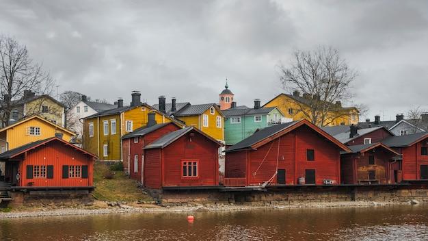 都市の景観。春にフィンランドのポルヴォー市の川の土手に赤い木造住宅