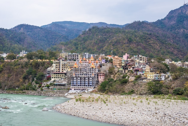 Cityscape of rishikesh at sunset, holy town and travel destination in india. colorful sky and clouds reflecting over the ganges river.