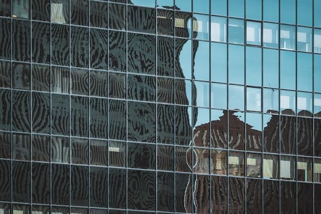 オフィスビルのガラス張りのファサードに映る街並みのシルエット
