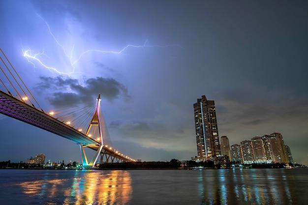 Cityscape urban bridge at night chao phraya river and lightning