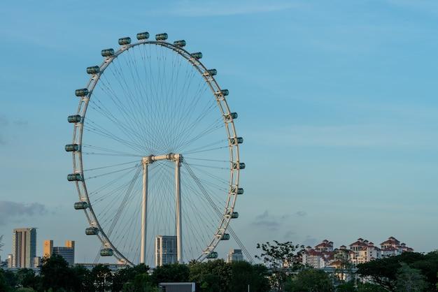 Городской вид на сингапур и сингапурский флаер на фоне голубого неба