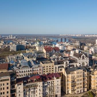 Вид городского пейзажа на современные здания в центре города, андреевскую церковь, подольский мост и левый берег города киев, украина. фото дрона