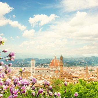 Cityscape with church santa maria del fiore at spring day with blooming magnolia, florence, italy