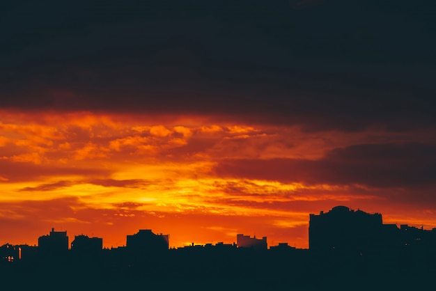 Cityscape with vivid fiery dawn. amazing warm dramatic cloudy sky above dark silhouettes of city buildings. orange sunlight. atmospheric background of sunrise in overcast weather. copyspace.
