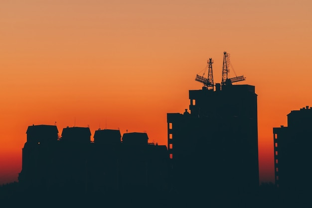 Cityscape with vivid fiery dawn. amazing warm dramatic cloudy sky above dark silhouettes of city buildings.