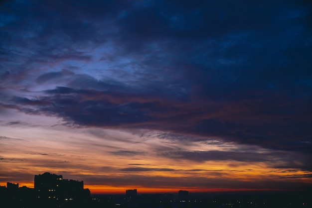 Cityscape with vivid warm dawn. amazing dramatic blue violet cloudy sky above dark silhouettes of city buildings. orange sunlight. atmospheric background of sunrise in overcast weather. copy space.