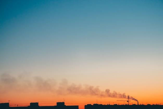 Городской пейзаж с прекрасным разноцветным ярким рассветом. удивительное голубое небо с оранжевым солнечным светом над темными силуэтами городских зданий.