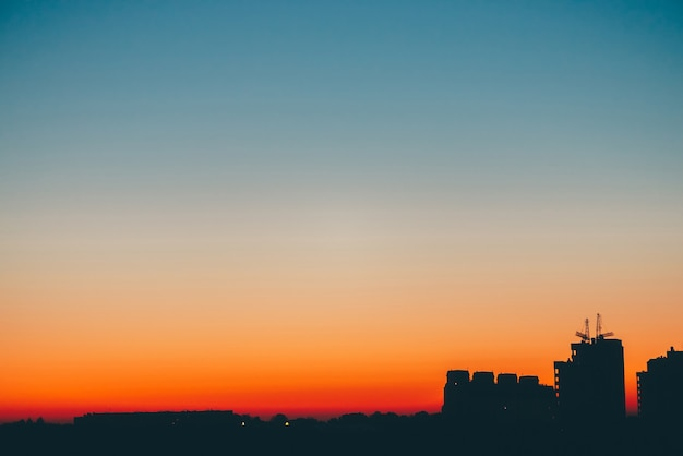 Cityscape with wonderful varicolored vivid dawn. amazing blue sky with orange sunny light above dark silhouettes of city buildings. atmospheric background of warm sunrise. copy space.