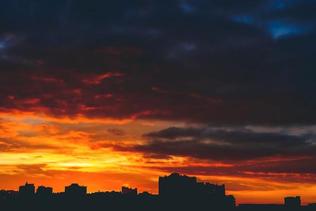 Городской пейзаж с прекрасным разноцветным ярким огненным рассветом. удивительное драматическое разноцветное облачное небо. темные силуэты городских зданий. атмосферная предпосылка восхода солнца в пасмурную погоду. копировать пространство
