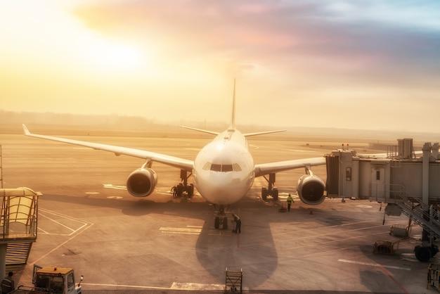 日没時の空港エプロンの民間旅客機