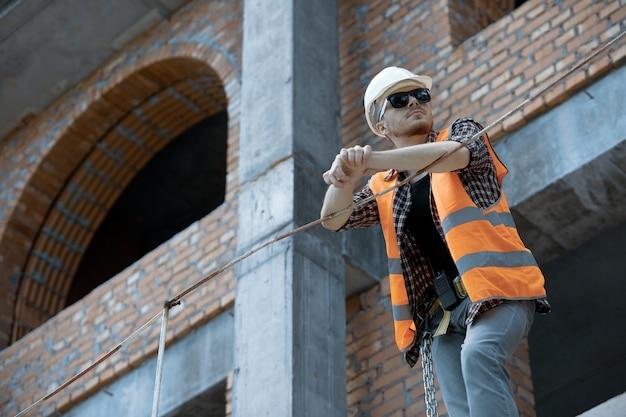 주황색 조끼 흰색 하드 모자와 선글라스의 높이에서 토목 기술자