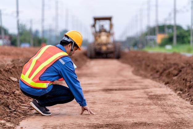 Инженер-строитель проверяет поверхность почвы и контролирует желтый вибрирующий грунт и автогрейдер civil