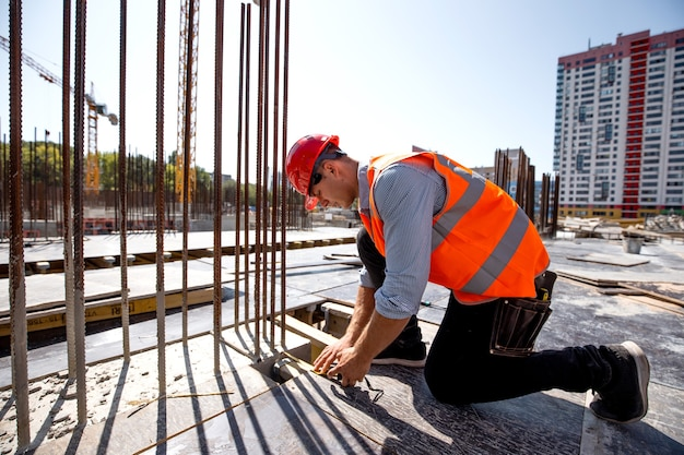 Civil engineer dressed in shirt, orange work vest and helmet measures the hole with a tape measure on the building site . .