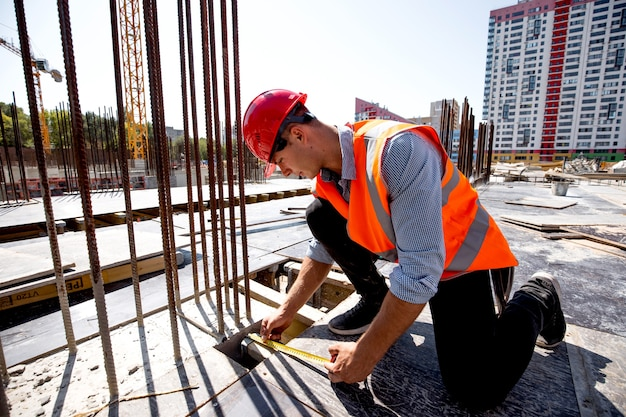 Civil engineer dressed in shirt, orange work vest and helmet measures the hole with a tape measure on the building site .