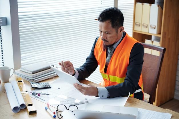 タブレットコンピュータの建設プロジェクトに関する情報を文書に記入する土木技師