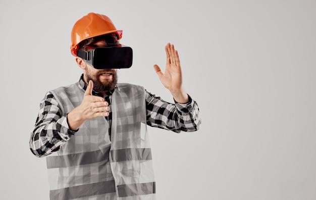 Инженер-строитель в оранжевом шлеме и в 3d-очках на свете.