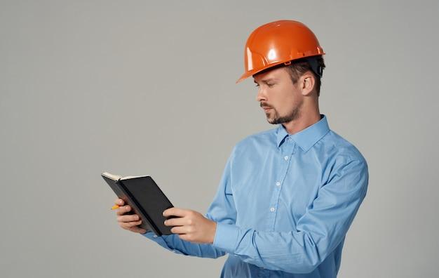 손 메모장 비즈니스 작업에 문서를 들고 주황색 모자에 토목 엔지니어.