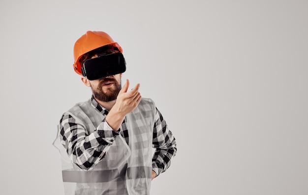 Инженер-строитель в оранжевой клетчатой рубашке шлема очки 3d показывать руками. фото высокого качества