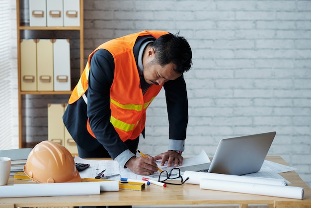 レンジベストの土木技師がオフィスのテーブルで建設計画を修正