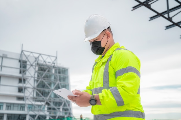 토목 기사는 태블릿에서 건설 현장 구조와 계획을 검사합니다. 토목 기사는 계획에 대해 실제 건설 현장을 검사합니다. 토목 기사는 건물을 검사하기 위해 태블릿을 들고 있습니다.