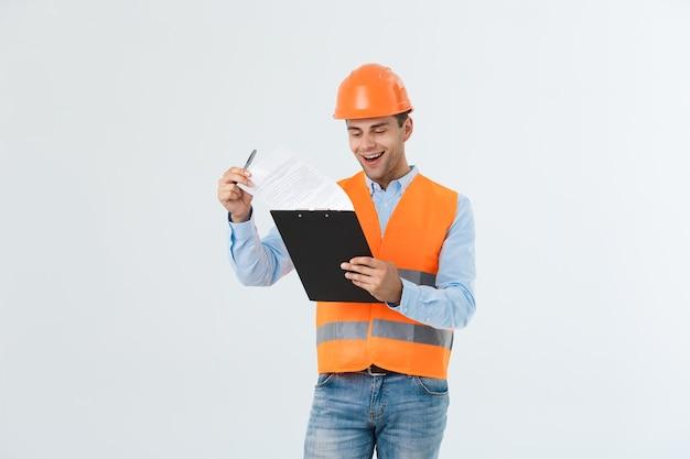 토목 기사 또는 건축 공학 및 안전 헬멧을 사용하여 건물, 엔지니어링 및 건축가 개념을 확인하는 작업자.