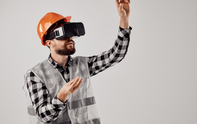 Civil engineer in an orange helmet and in 3d glasses on a light space
