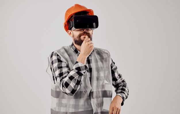 Civil engineer wearing 3d virtual reality glasses and an orange hard hat on his head. high quality photo