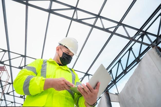 마스크를 쓴 토목 기사는 노트북으로 건설 현장 구조와 계획을 검사합니다. 토목 기사는 실제 건설 현장을 검사합니다. 토목 기사는 건물을 검사하기 위해 노트북을 들고 있습니다.