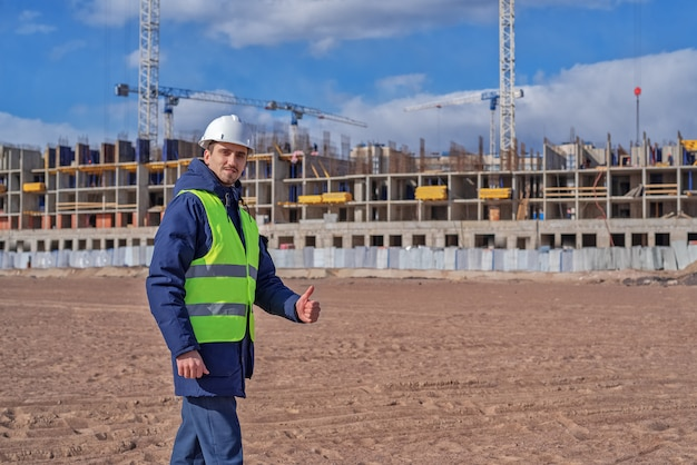 Civil engineer in a white helmet and blue jacket on the site