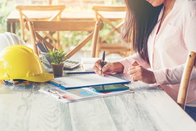 Инженер-строитель работает на офисном столе с деловыми штучками и инженерной защитой. инженерно-промышленная концепция.