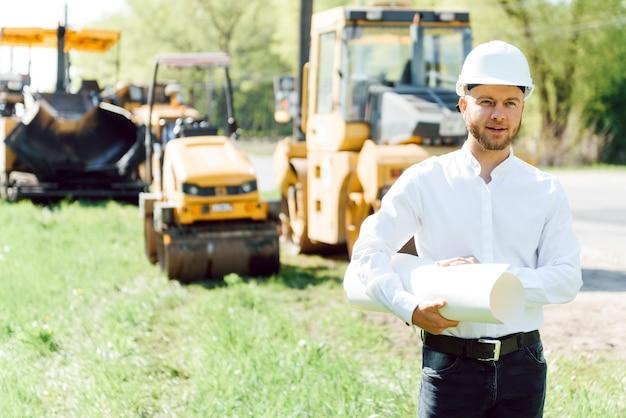 Гражданское строительство, дорожное строительство. концепция строительства новой асфальтированной дороги. ремонт дорог. работник дорожной службы возле катка.