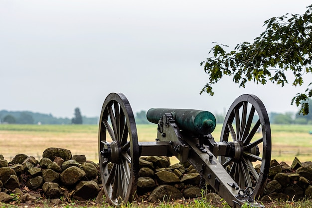 A civil war era cannon is placed behind a stone wall in gettysburg