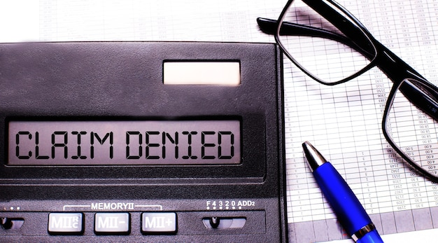 Claim denied is written in the calculator near black-framed glasses and a blue pen.