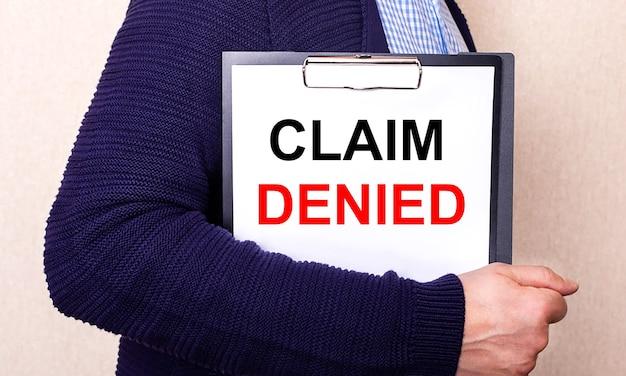 Заявление отказано написано на белом листе, который держит человек, стоящий боком.