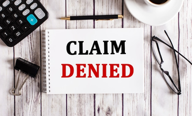 Claim denied is written in a white notepad near a calculator, coffee, glasses and a pen. business concept