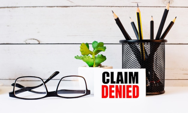 Claim denied written on a white business card next to pencils in a stand and glasses. nearby is a potted plant.