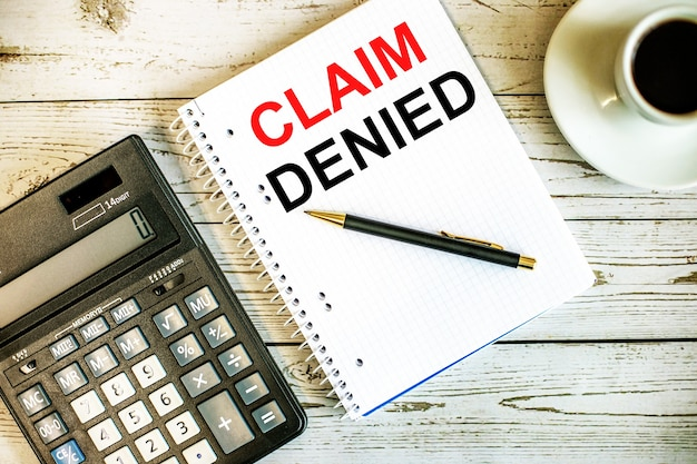 Claim denied written on white paper near coffee and calculator on a light wooden table