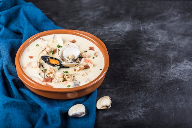 Clam chowder in a brown plate. the main ingredients are shellfish, broth, butter, potatoes and onions.