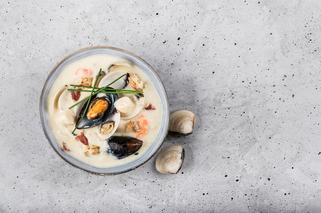 Clam chowder in a gray plate. the main ingredients are shellfish, broth, butter, potatoes and onions.