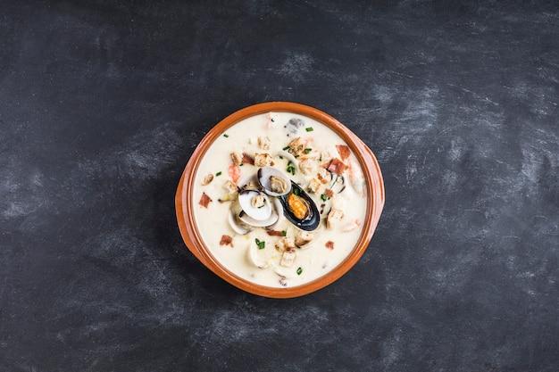 茶色のプレートにクラムチャウダー。主な材料は貝、スープ、バター、ジャガイモ、タマネギです。