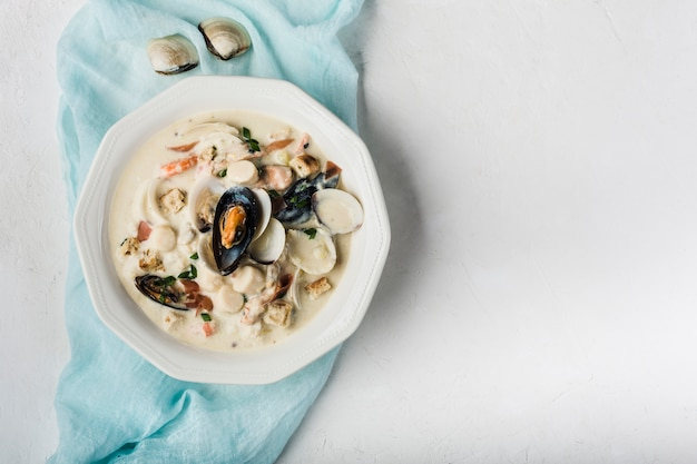 Clam chowder in a white plate. the main ingredients are shellfish, broth, butter, potatoes and onions.