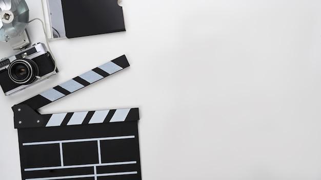 Обшивка, фотоаппарат и копией пространства на белом фоне.