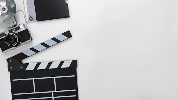 Clapboard, camera and copy space on white background.