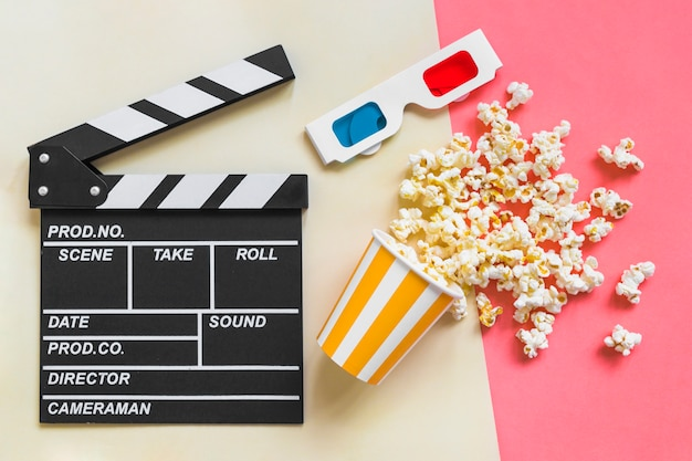 Clapboard near 3d glasses and popcorn
