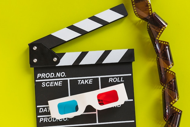 Clapboard near carton 3d glasses and tape
