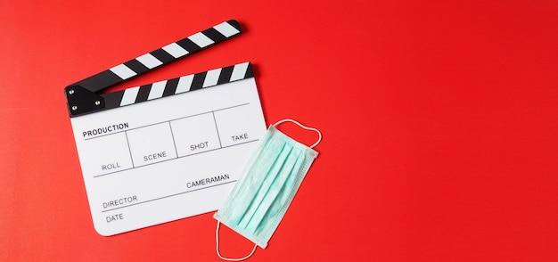 빨간색 배경에 클래퍼 보드와 얼굴 마스크입니다. 비디오 제작이나 영화 및 영화 산업에서 사용됩니다.