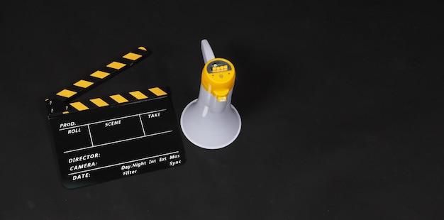 클래퍼 보드와 확성기는 검정색 배경에 노란색으로 분리되어 있습니다.